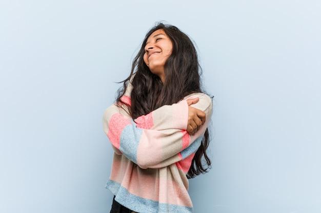 La mujer india de la moda joven se abraza, sonriendo despreocupada y feliz.