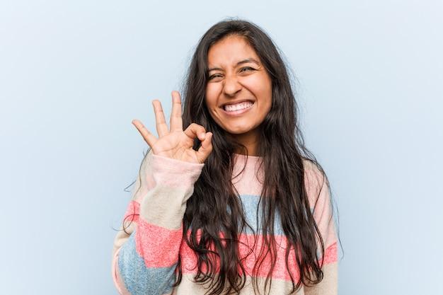 La mujer india de la moda joven guiña un ojo y lleva a cabo un gesto aceptable con la mano.
