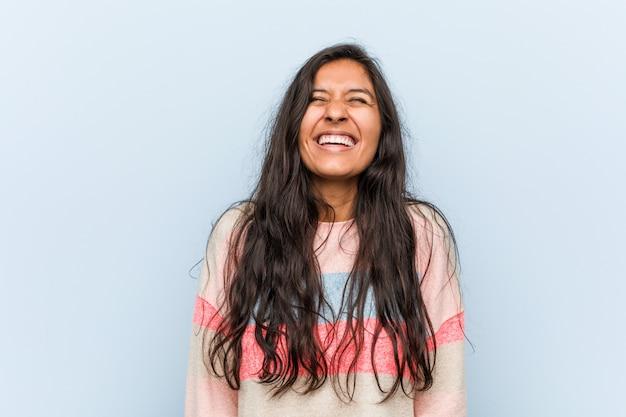 La mujer india de la moda joven se ríe y cierra los ojos, se siente relajada y feliz.