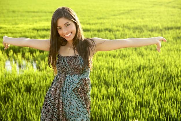 Mujer india morena hermosa en campos de arroz verde