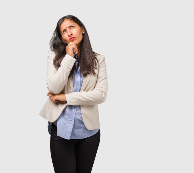 Mujer india del negocio joven que piensa y que mira para arriba