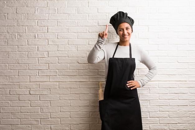Mujer india del panadero joven contra una pared de ladrillos que muestra el número uno, símbolo de contar, concepto de matemáticas, confiado y alegre