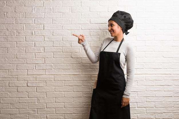 Mujer india del panadero joven contra una pared de ladrillos que señala al lado.