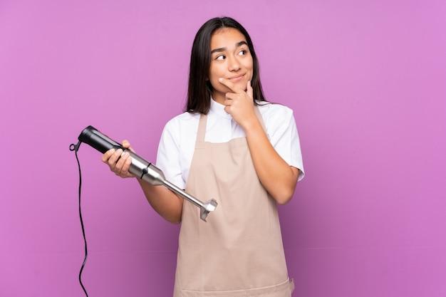 Mujer india que usa la licuadora de mano aislada en la pared púrpura que piensa una idea