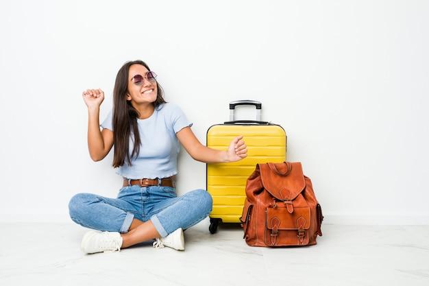 Mujer india de raza mixta joven lista para ir a viajar bailando y divirtiéndose.