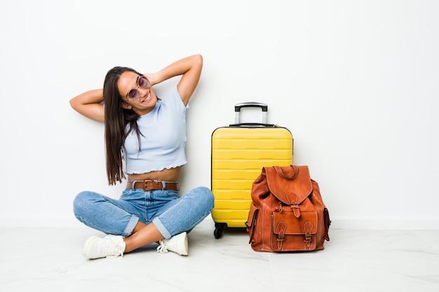Mujer india de raza mixta joven lista para viajar estirando los brazos, posición relajada.