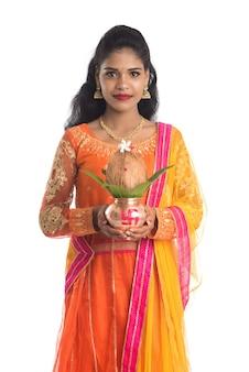 Mujer india sosteniendo un tradicional kalash de cobre con hojas de coco y mango con decoración floral