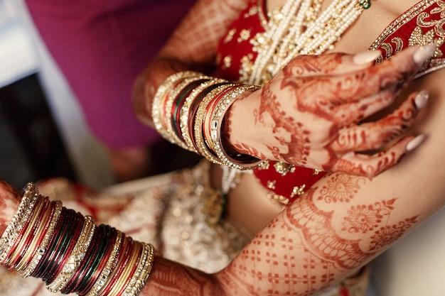 La mujer india sostiene sus manos cubiertas con mehndi