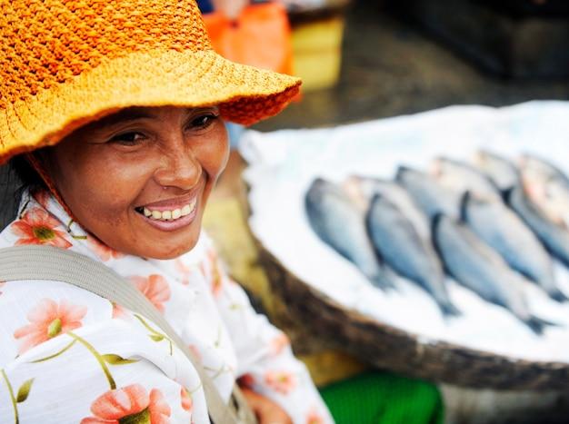 Mujer indígena camboyana vendiendo pescado en un mercado.