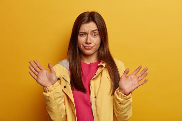 Mujer indignada y despistada levanta las palmas de las manos, posa indiferente, tiene expresión desconcertada y vacilante, insatisfecha con algo, vestida con chaqueta amarilla, posa en interiores. concepto de reacción y emociones humanas