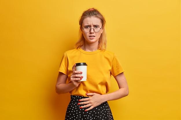 Mujer infeliz disgustada frunce el ceño, se siente mal, mantiene la mano en el vientre, bebe café para llevar, comió comida en mal estado, usa lentes transparentes, camiseta amarilla informal
