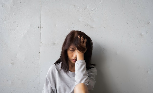 Mujer infeliz con la mano en la cabeza, malestar y sentimiento de tristeza