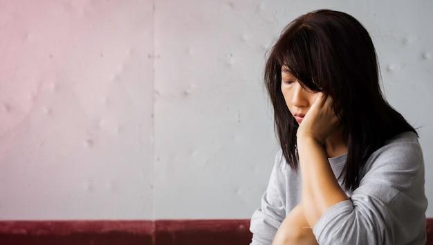 Mujer infeliz con la mano en la cara, con malestar y sentimiento triste