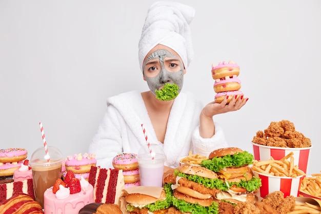 Mujer infeliz se siente cansada de las restricciones alimenticias mantiene la dieta sostiene un montón de deliciosas y apetitosas donas tiene la boca atascada con ensalada verde evita consumir comida rápida