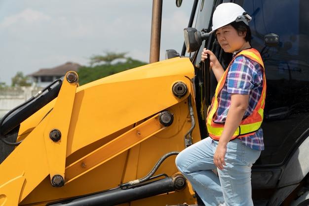 Mujer ingeniería vistiendo un casco de seguridad blanco de pie delante de la retroexcavadora