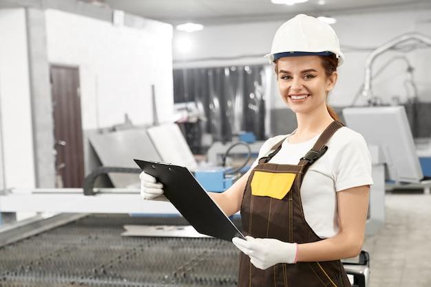 Mujer ingeniero en casco y batas posando en fábrica.