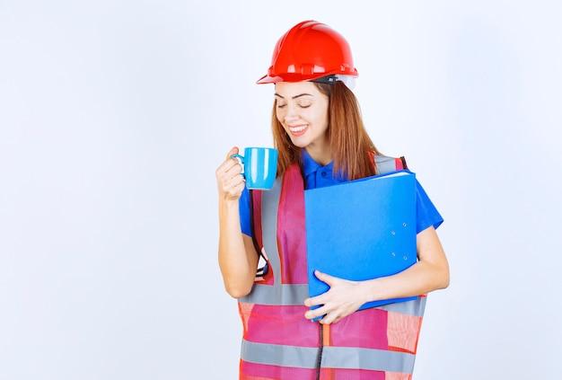 Mujer ingeniero en casco rojo sosteniendo una carpeta azul y tomando una taza de bebida.