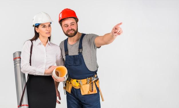 Mujer ingeniero y constructor apuntando hacia afuera