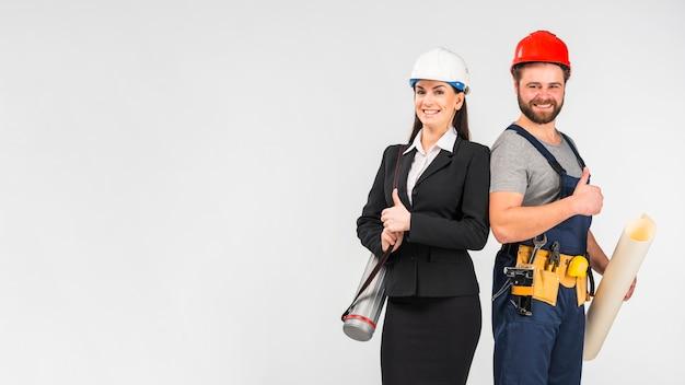 Mujer ingeniero y constructor mostrando los pulgares para arriba