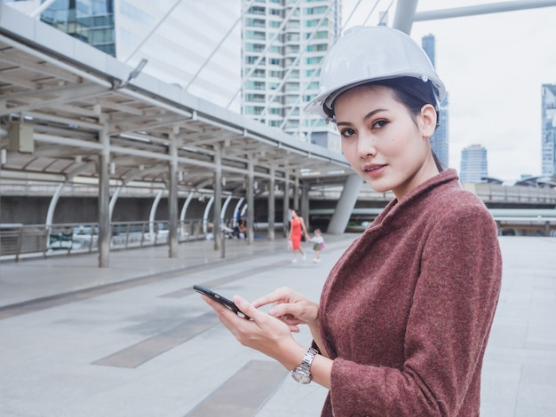 Mujer ingeniero usar teléfono en ciudad