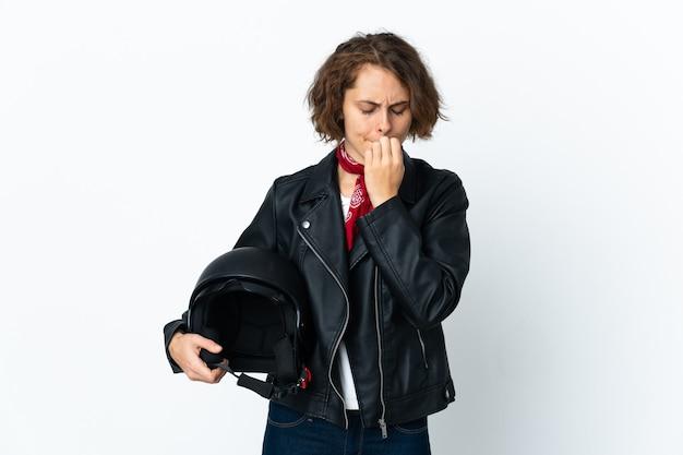 Mujer inglesa sosteniendo un casco de motocicleta aislado en la pared blanca teniendo dudas