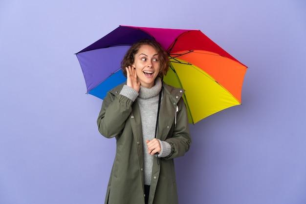 Mujer inglesa sosteniendo un paraguas aislado en la pared púrpura escuchando algo poniendo la mano en la oreja