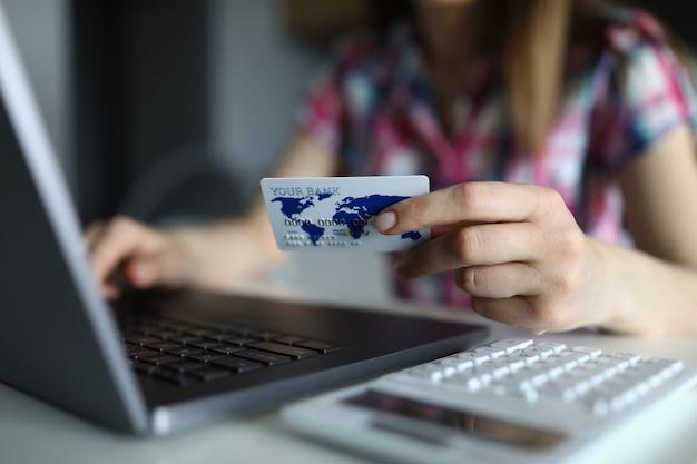 La mujer ingresa los detalles de la tarjeta de crédito en la computadora portátil