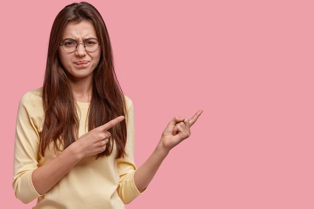 Una mujer insatisfecha no impresionado frunce el ceño con disgusto, apunta a la derecha con ambos dedos índices