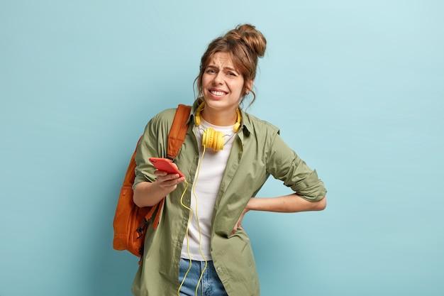 Mujer insatisfecha sonríe, mantiene la mano en la espalda, sufre de un dolor terrible mientras lleva una mochila pesada, vestida de manera informal