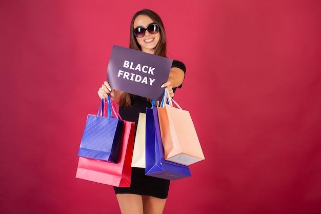 Mujer con inscripción de black friday y bolsas de compras