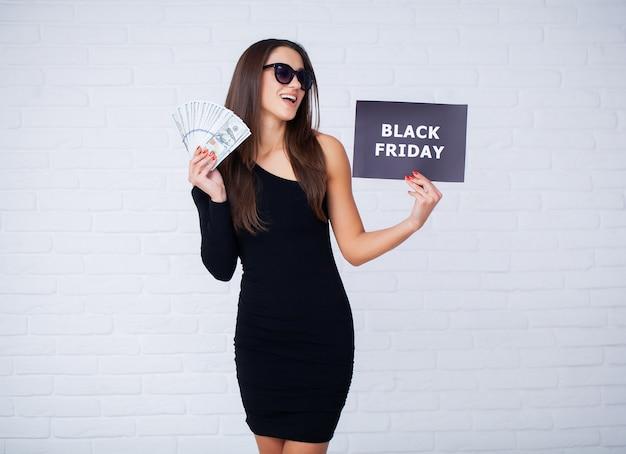 Mujer con inscripción de black friday y dinero