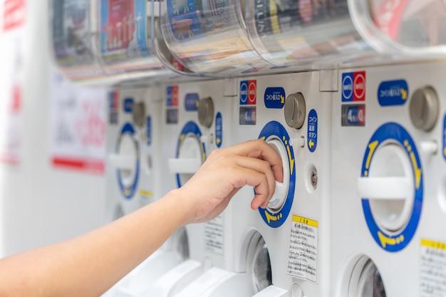 La mujer inserta la máquina de monedas a cápsulas