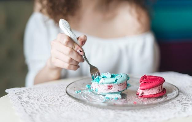 Mujer insertando el tenedor en el sándwich de helado en un plato sobre la mesa
