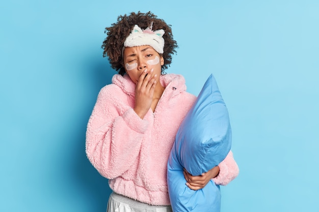 Mujer insomne agotada tiene el pelo rizado bosteza cubre la boca vestida con ropa de dormir sostiene almohada quiere dormir se despierta muy temprano aislado sobre una pared azul