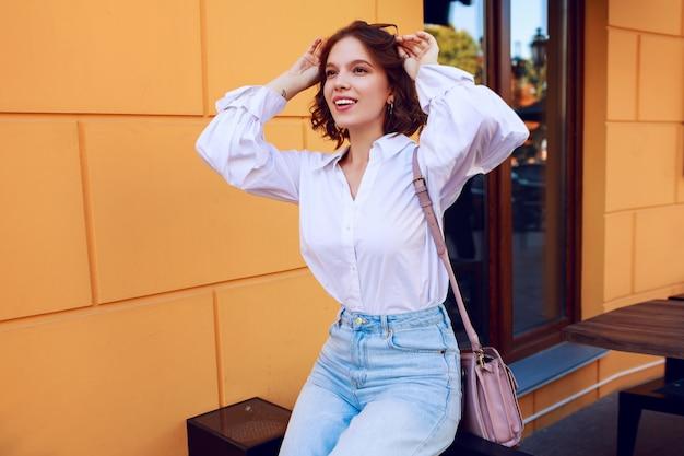 Mujer inspirada con pelos de camisa disfrutando los fines de semana en la soleada ciudad europea. blusa casual.