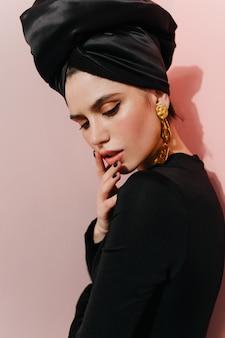 Mujer inspirada en turbante negro mirando hacia abajo