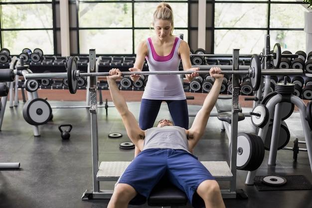 Mujer del instructor que ayuda al hombre atlético en gimnasio