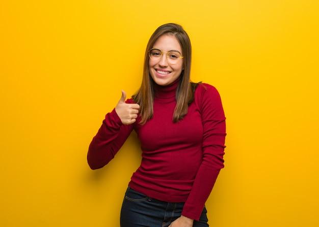 Mujer intelectual joven que sonríe y que levanta el pulgar para arriba