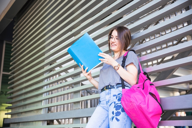 Mujer inteligente leyendo libros de texto en la universidad