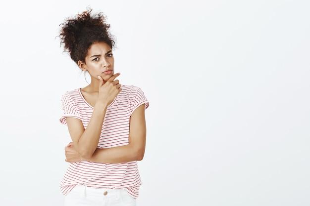 Mujer inteligente con peinado afro posando en el estudio
