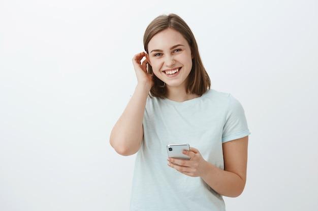 Mujer intercambiando números con chico lindo en festival. encantadora chica joven de aspecto amistoso moviendo el cabello detrás de la oreja coqueta y riendo mientras mira sosteniendo el teléfono inteligente contra la pared gris