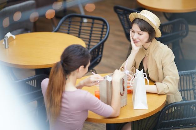 Mujer intercambiando regalos en la cafetería