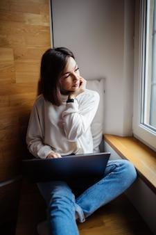 La mujer interesada está trabajando en la computadora portátil mientras está sentada en una amplia ventana en el tiempo diario