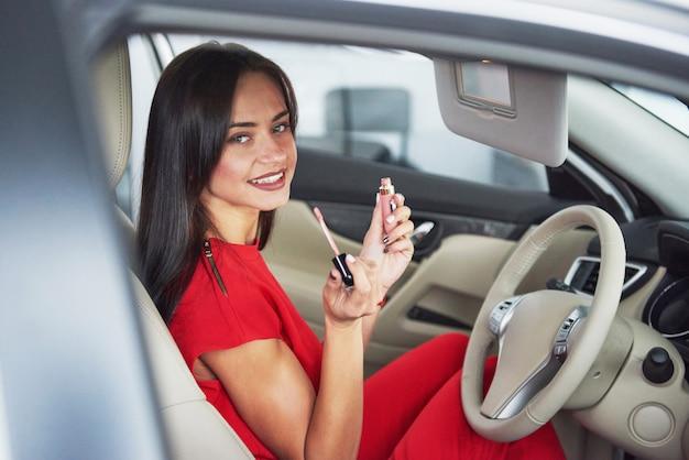 La mujer en el interior del coche mantiene la rueda girando sonriendo mirando a los pasajeros en el asiento trasero idea conductor del taxi contra los rayos del sol cielo de brillo ligero concepto de examen vehículo