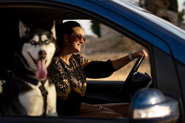 Mujer en el interior del vehículo con su perro husky siberiano.