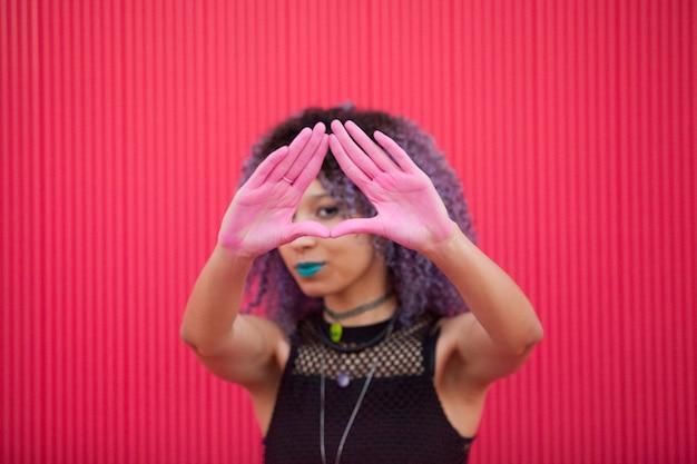 Mujer interracial con manos manchadas en polvo rosa