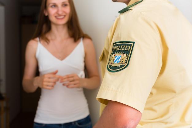 Mujer de interrogación de oficial de policía en la puerta