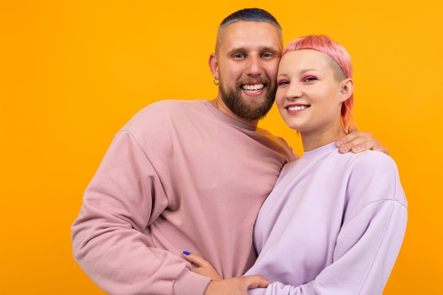 Mujer inusual con cabello rosado corto y abrazos de tatuaje con su novio aislado en naranja
