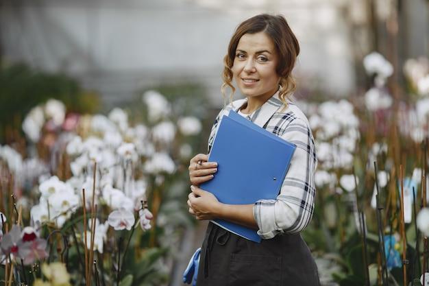 Mujer en invernadero. trabajador comprueba flores. chica con carpeta