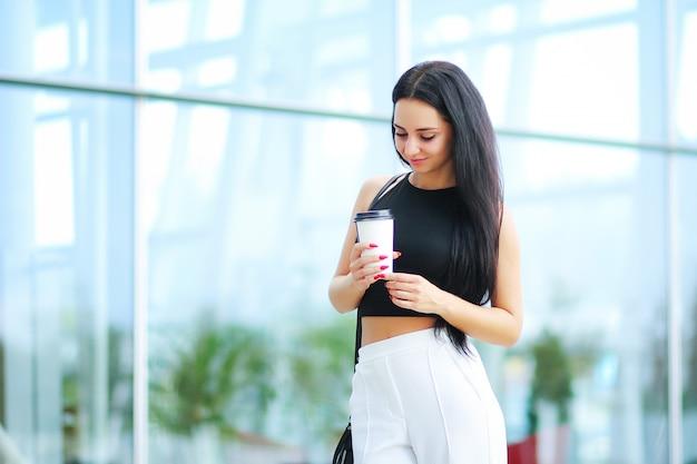 Mujer ir de viaje con equipaje en el aeropuerto internacional de lviv y tomar un café